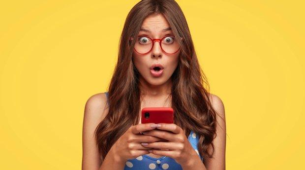 Frau mit überraschtem Gesichtsausdruck hält Handy in der Hand.