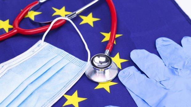 Mund-Nasen-Schutz, Stethoskop, Handschuhe auf Flagge der EU.