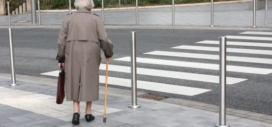 eine person will die fahrbahn auf dem fußgängerüberweg überqueren
